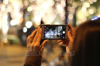 女性,1人,冬,カメラ,夜,スマホ,光,イルミネーション,ライトアップ,人,スマートフォン,玉ボケ,グランフロント,携帯電話,ぼやける,シャンパンゴールド