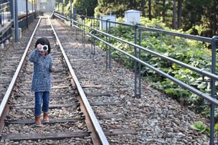 鉄道トラックの上に立って小さな男の子の写真・画像素材[1830857]
