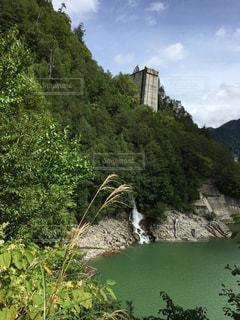 近くに水の体の横にある丘の中腹のアップの写真・画像素材[1454737]