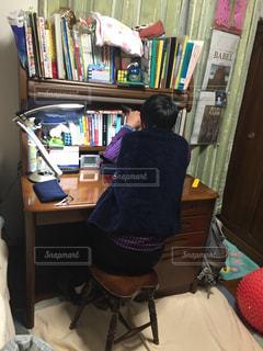 本棚の前の机に座っている人の写真・画像素材[2817639]