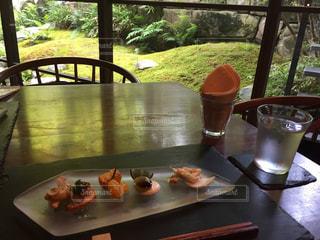 木製のテーブルの上に食べ物の皿とビールのグラスの写真・画像素材[2871338]