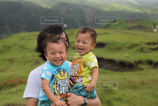 阿蘇山で父親に抱っこされる双子の男の子の写真・画像素材[1404275]