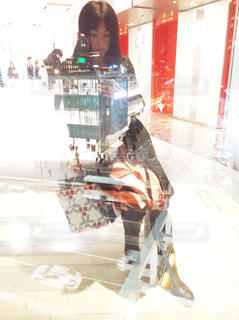 女性,30代,ファッション,夜景,ビル,コート,車,窓,スマホ,黒髪,スカート,都会,スマートフォン,新宿,模様,携帯,ショッピング,待ち合わせ,柄,冬服,ロングブーツ