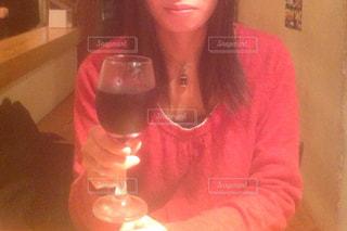 ワイングラスを持つテーブルに座っている女性 - No.877146