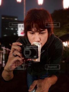 カメラを構える真剣な眼差しと、裏腹なビール。の写真・画像素材[894772]