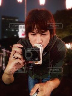 カメラを構える真剣な眼差しと、裏腹なビール。の写真・画像素材[902173]