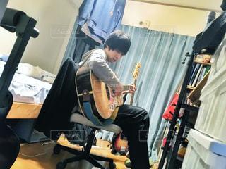 男性,屋内,部屋,室内,ギター,人物,座る,くつろぐ,楽器,音楽,のんびり,休息,弾き語り,アコースティック,休みの日,演奏する