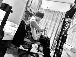 男性,屋内,モノクロ,部屋,室内,ギター,人物,座る,くつろぐ,楽器,音楽,のんびり,休息,弾き語り,アコースティック,休みの日,演奏する