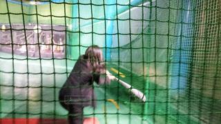 女性,スポーツ,屋内,後ろ姿,躍動感,野球,運動,アミューズメント,娯楽,バッティングセンター,バッティング,スピード感,ストレス解消