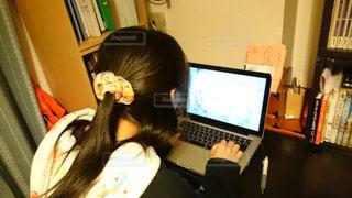 ノート パソコンの前で机に座っている女性の写真・画像素材[1531732]