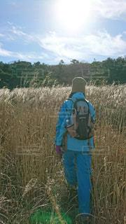 草の覆われてフィールド上に立っている人の写真・画像素材[1408559]