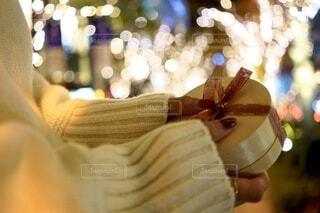 イルミネーションがきれいな場所でプレゼントを渡す女性手元の写真・画像素材[3934377]