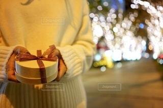 イルミネーションがきれいな場所でプレゼントを渡す女性の写真・画像素材[3934376]