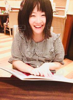 テーブルに座っている笑顔の女の子の写真・画像素材[1374649]