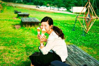 公園のベンチに座っている女の子の写真・画像素材[1366673]