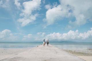 水の体の近くのビーチに人々 のカップルの写真・画像素材[1393473]