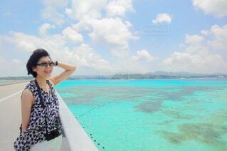 透き通る海と橋の上で爽やかな風を受ける女性の写真・画像素材[4562216]