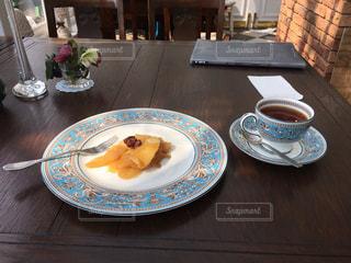 木製テーブルの上に座っている青と白のプレートの写真・画像素材[1425968]