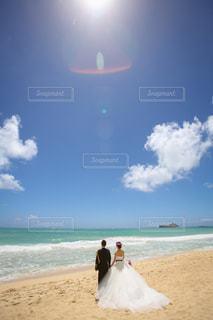 海の横にある砂浜のビーチの上に立っている人の写真・画像素材[1386700]