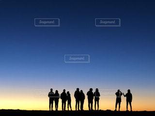 日没の前に立っている人々のグループの写真・画像素材[2135194]