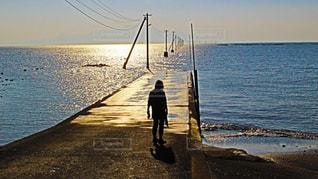 水の体の横に立っている人の写真・画像素材[853341]