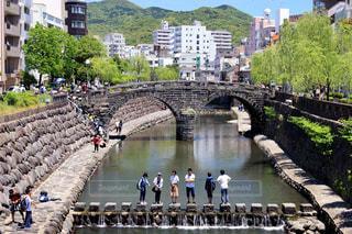 水の体の上の橋を渡って歩いている人々 のグループの写真・画像素材[853349]