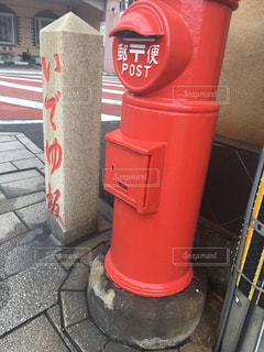 建物の側に座っている赤い消火栓の写真・画像素材[1395046]