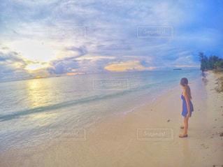 水の体の近くのビーチに立っている人の写真・画像素材[1394879]