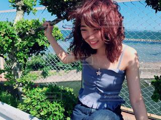 フェンスの前に立っている女性の写真・画像素材[1401769]