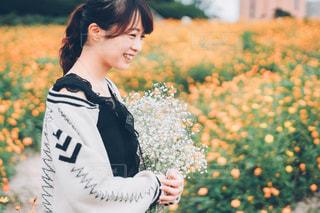 花の前に立っている女性の写真・画像素材[1595532]
