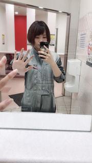 カメラにポーズ鏡の前に立っている人の写真・画像素材[1714573]
