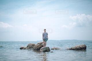 水の体の隣に立っている男の写真・画像素材[3620917]
