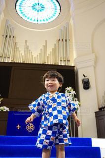 青い壁の前に立っている少年の写真・画像素材[1415034]