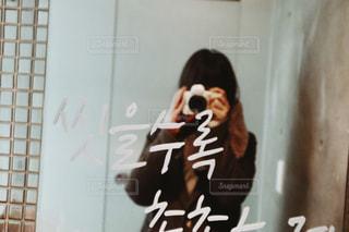 カメラにポーズ鏡の前に立っている人の写真・画像素材[1830143]