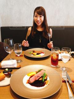 食品のプレートをテーブルに座っている女性の写真・画像素材[1464436]