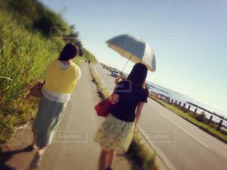 海,空,夏,屋外,緑,後ろ姿,海辺,散歩,道路,女の子,草,外,道,日傘,レジャー,友達,お出かけ