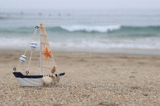 砂浜の上のヨットの置物と波の写真・画像素材[2330233]