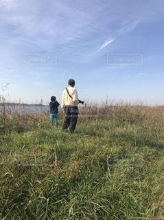 芝生のフィールドに立っている男の写真・画像素材[1716989]