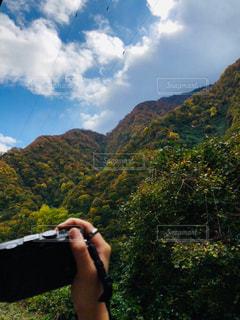 山の前に立っている人の写真・画像素材[1617327]