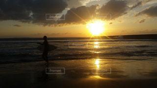 バック グラウンドで夕焼けのビーチに立っている人の写真・画像素材[1512908]