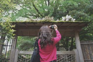 フェンスの前に立っている女の子の写真・画像素材[1830049]