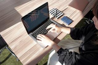 ノートパソコンを使って木製のテーブルに座っている人の写真・画像素材[2327571]