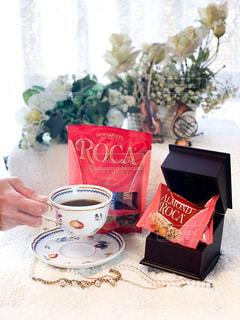 テーブルの上にコーヒーと花瓶1本の写真・画像素材[2847547]