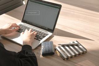 木製のテーブルの上に座っているラップトップコンピュータを使用している人の写真・画像素材[2984383]