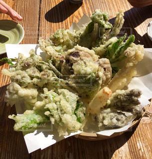 近くの木製のテーブルの上に食べ物をの写真・画像素材[1640546]
