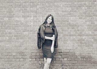 レンガの壁の前に立つ女性の写真・画像素材[2391413]