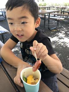 ピクニック用のテーブルに座っている小さな男の子の写真・画像素材[1447964]