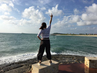 水の体の近くのビーチに空気を通って飛んで男の写真・画像素材[1591969]