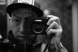 鏡の前で帽子をかぶった男がカメラに向かってポーズをとるの写真・画像素材[2269678]