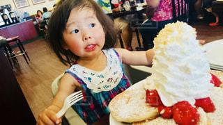 テーブルの上に座っているケーキの一部を保持している小さな女の子の写真・画像素材[1452476]